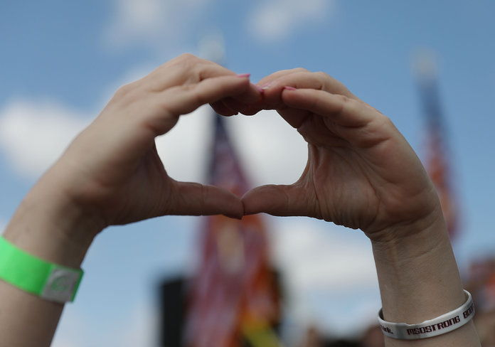 А heart-shaped symbol of hope is formed with two hands.
