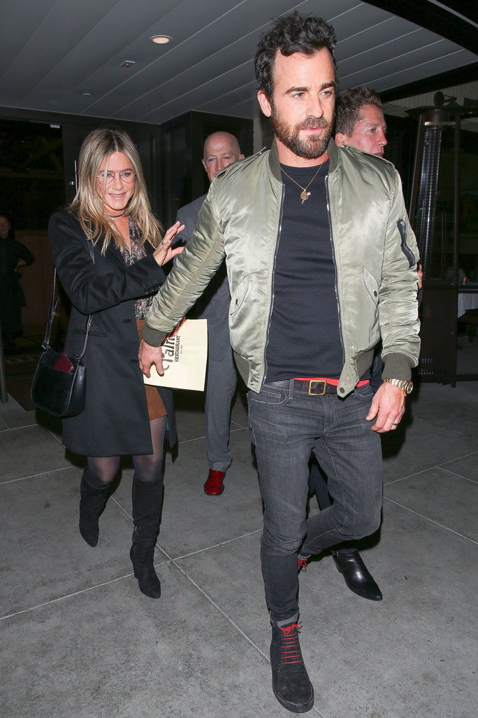 Јеннифер Aniston and husband Justin Theroux enjoy a romantic date night out at The Palm restaurant in Beverly Hills. Jennifer has a huge smile on her face as she leaves with her man. Justin reaches back for her, and they hold hands as they head to the car